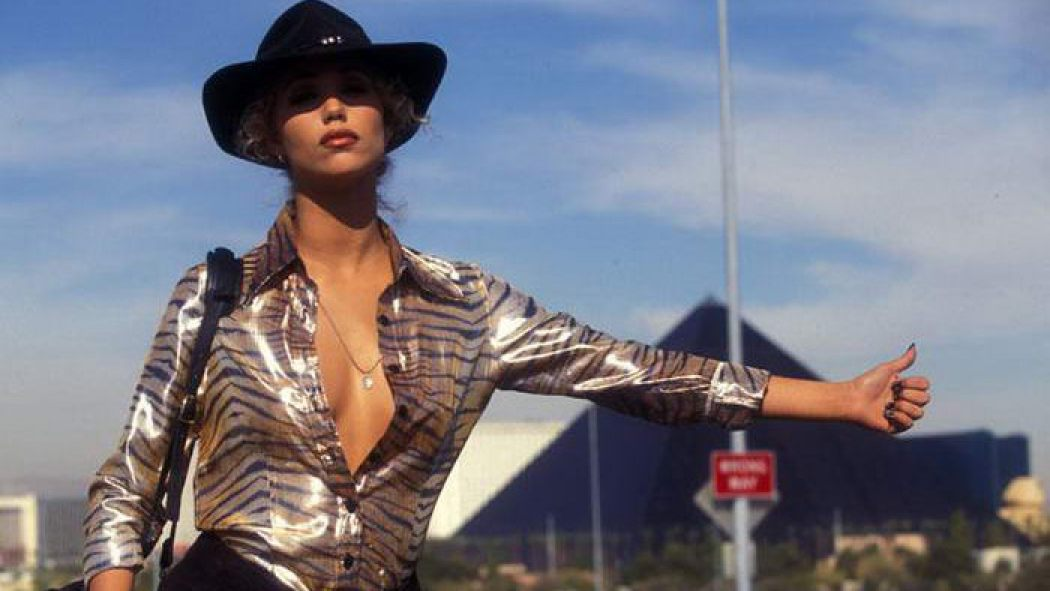 Showgirls (1995). Nomi, a blonde white woman stands on the side of a highway, her thumb stuck out to gesture that she wants to hitch a ride. She wears a shiny zebra-print shirt unbuttoned almost to her waist, and a black cowboy hat. She has a bag slung over her shoulder.